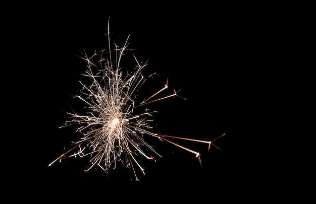 Glitzernde brennende wunderkerze im dunkeln. funken. weihnachten und neujahr. magisches licht Premium Fotos