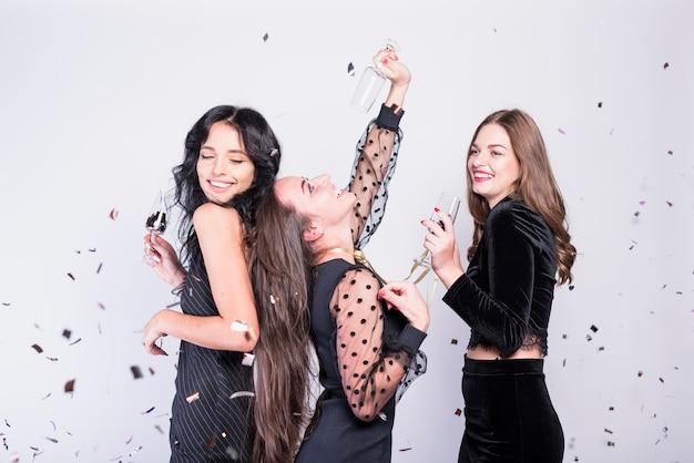 Glückliche Frauen, die mit Gläsern Champagner tanzen Kostenlose Fotos