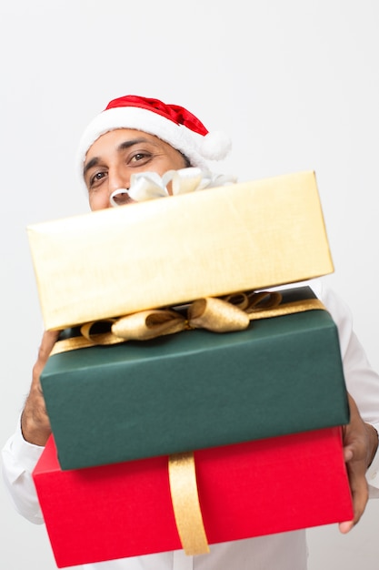Glücklicher netter Mann in Sankt-Hut, der Stapel Geschenke hält ...
