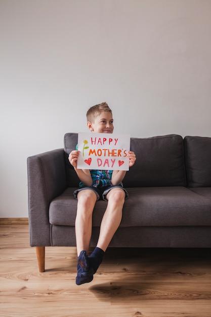gl ckliches kind mit muttertag zeichen auf einer couch sitzen download der kostenlosen fotos. Black Bedroom Furniture Sets. Home Design Ideas