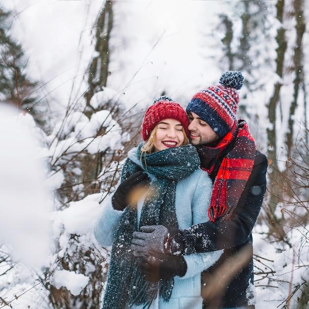 Glückliches Paar im Winterwald umarmen Kostenlose Fotos