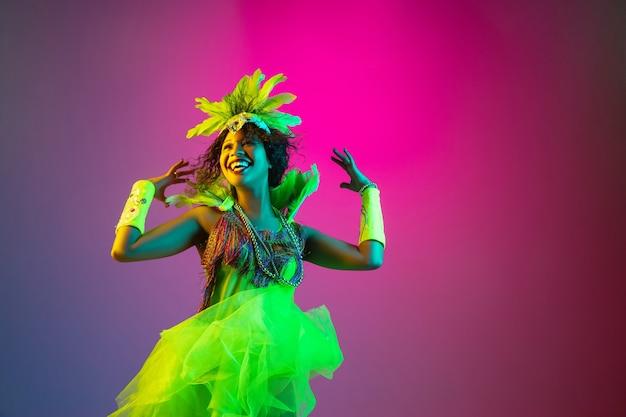 Glück. schöne junge frau im karneval, stilvolles maskeradenkostüm mit federn, die auf gradientenwand im neonlicht tanzen. konzept der feiertagsfeier, festlich, tanz, party, spaß haben. Kostenlose Fotos