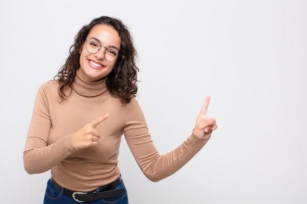 Glücklich lächelnd und mit beiden händen zur seite und nach oben zeigend, zeigt das objekt im kopierraum Premium Fotos