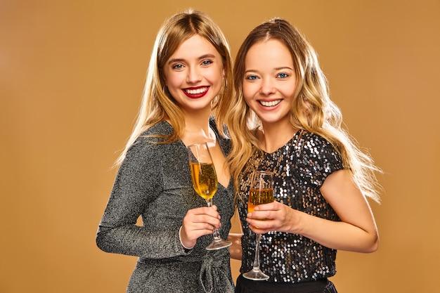Glücklich lächelnde frauen in stilvollen glamourösen kleidern mit champagnergläsern Kostenlose Fotos