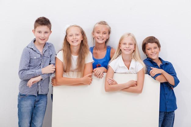 Glücklich lächelnde gruppe von kindern, jungen und mädchen, zeigt brett Kostenlose Fotos