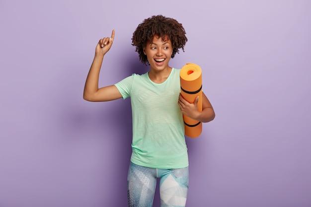 Glücklich lächelnde sorglose lockige afroamerikanische sportlerin trägt zerknitterte yogamatte, hebt den arm und zeigt nach oben, genießt gutes training, trägt t-shirt und leggings. sportkonzept Kostenlose Fotos