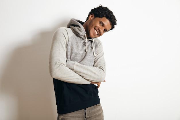 Glücklich lächelnder latino-typ trägt leeren grauen schwarzen pullover mit kapuze und notleidender jeans, kreuzt seine hände auf der brust, isoliert auf weiß Kostenlose Fotos