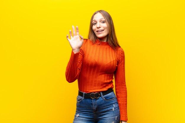 Glücklich und fröhlich lächeln, mit der hand winken, dich begrüßen und begrüßen oder sich verabschieden Premium Fotos