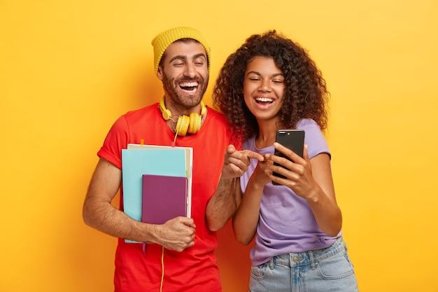 Glücklich verschiedene schüler schauen glücklich auf smartphone-gerät, halten notizblock, tragen stilvolle helle kleidung Kostenlose Fotos