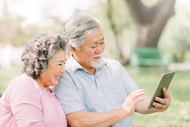 Glückliche ältere asiatische paare, die digitale tablette verwenden Premium Fotos