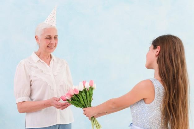 Glückliche ältere frau, die blumenstrauß von tulpenblumen von ihrem enkelkind empfängt Kostenlose Fotos