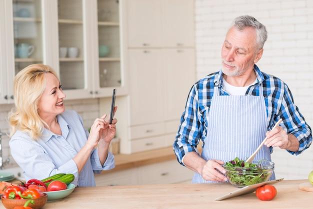 Glückliche ältere frau, die foto ihres ehemanns den salat in der schüssel zubereitet macht Kostenlose Fotos