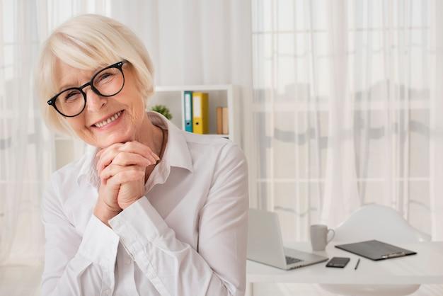 Glückliche ältere frau, die in ihrem büro steht Kostenlose Fotos