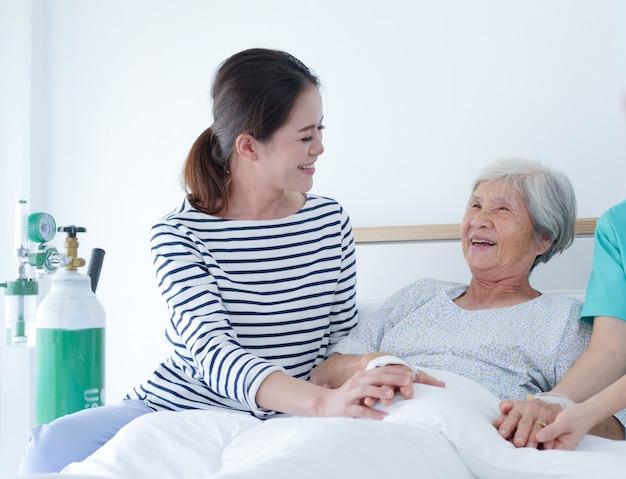 Glückliche ältere frau, die mit älterer krankenschwester und ihrer tochter im krankenhauszimmer spricht. Premium Fotos