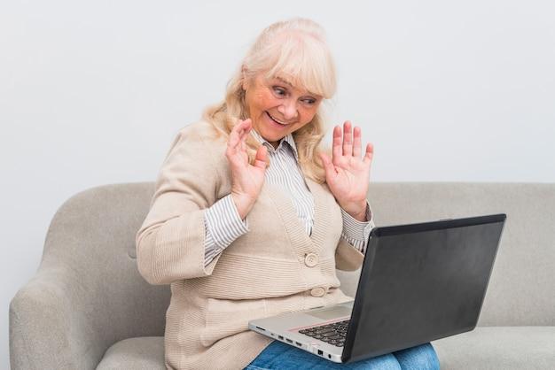 Glückliche ältere frau, die videochat auf wellenartig bewegender hand des laptops hat Kostenlose Fotos