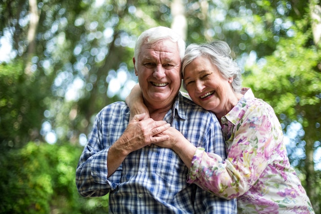 Glückliche ältere frau, die von hinten ehemann gegen bäume umfasst Premium Fotos
