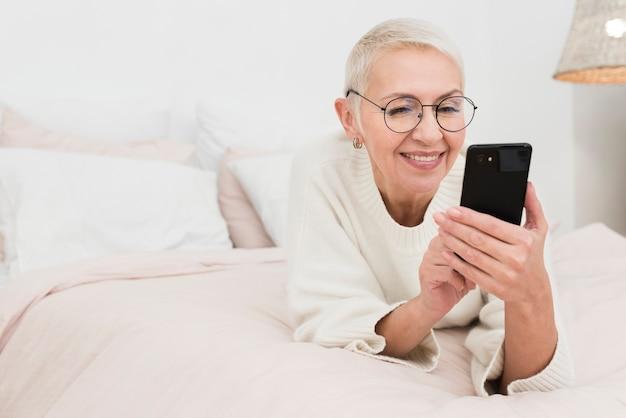 Glückliche ältere frau im bett, das smartphones hält Kostenlose Fotos