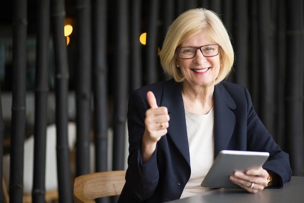 Glückliche ältere frau mit tablette im cafe Kostenlose Fotos