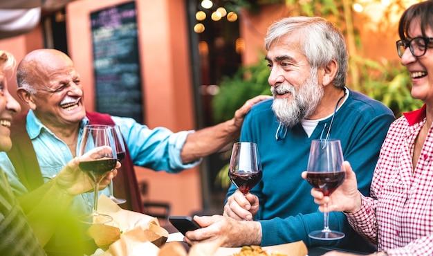 Glückliche ältere freunde, die spaß haben, rotwein auf der dinnerparty zu trinken Premium Fotos