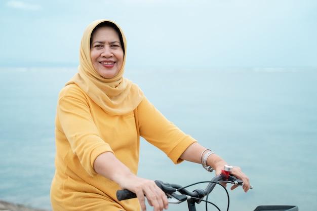 Glückliche ältere muslimische frau, die fahrrad fährt Premium Fotos