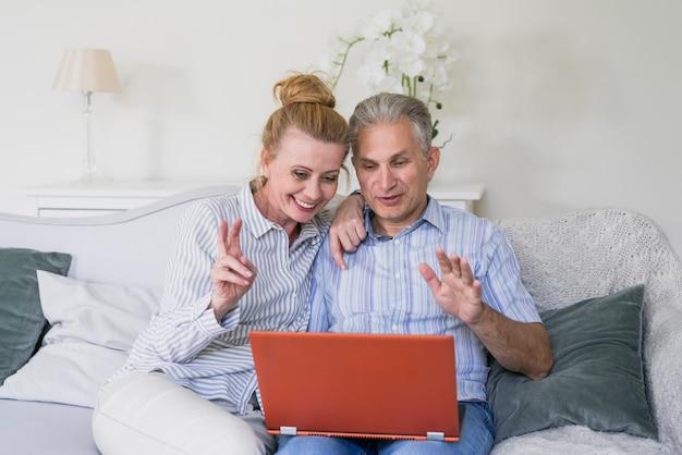 Glückliche ältere paare der vorderansicht mit laptop Kostenlose Fotos
