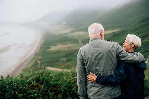 Glückliche ältere paare, die eine atemberaubende ansicht genießen Kostenlose Fotos