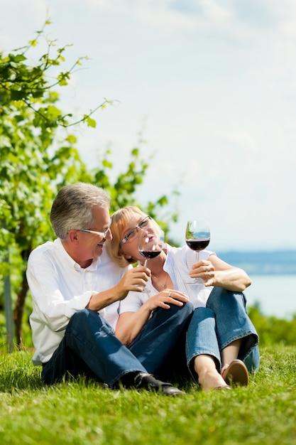 Glückliche ältere paare, die im trinkenden wein des grases sitzen Premium Fotos