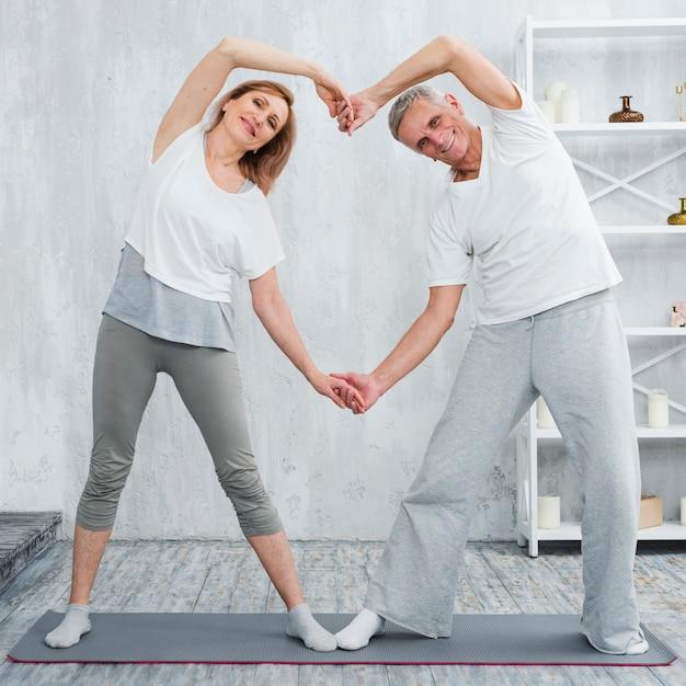 Glückliche ältere paare, die zu hause auf yogamatte stehen Kostenlose Fotos