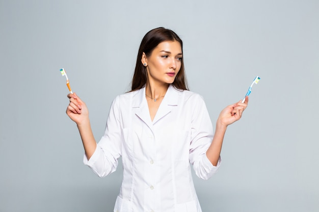 Glückliche ärztin, die zahnbürsten lokalisiert auf weißer wand hält Kostenlose Fotos