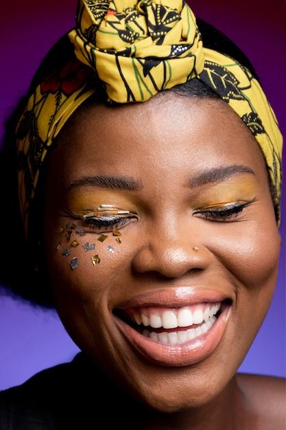 Glückliche afrikanische frau in der lederweste mit glänzendem konfetti auf ihren wangen Kostenlose Fotos