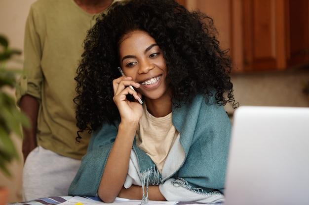 Glückliche afrikanische hausfrau, die handy hält und mit ihrer freundin spricht, am küchentisch sitzt, familienfinanzen verwaltet, laptop-pc benutzt, ihr mann mit händen in den taschen hinter ihr steht Kostenlose Fotos