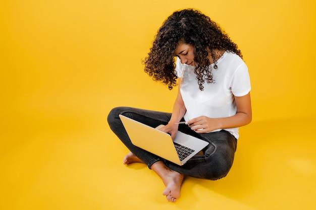 Glückliche afrikanische schwarze frau, die mit dem laptop und kreditkarte getrennt über gelb sitzt Premium Fotos