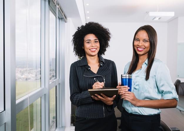 Glückliche afroamerikanerfrauen mit dokumenten und thermosflasche nahe fenster im büro Kostenlose Fotos