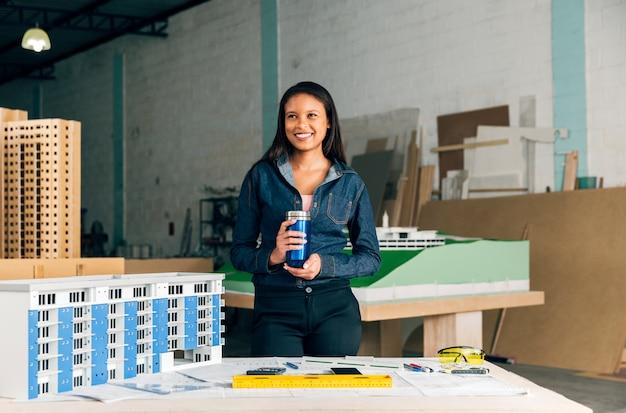 Glückliche afroamerikanische dame mit der thermosflasche, die nahe modell des gebäudes steht Kostenlose Fotos