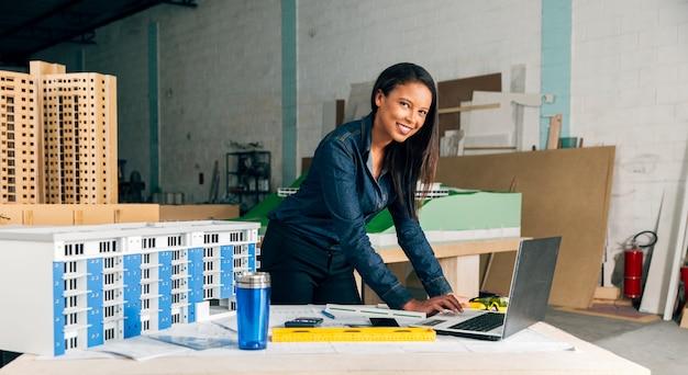 Glückliche afroamerikanische dame mit laptop und modell des gebäudes auf tabelle Kostenlose Fotos