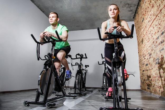 Glückliche aktive paare, die mit fahrrädern in einer turnhalle trainieren. vorderansicht Premium Fotos