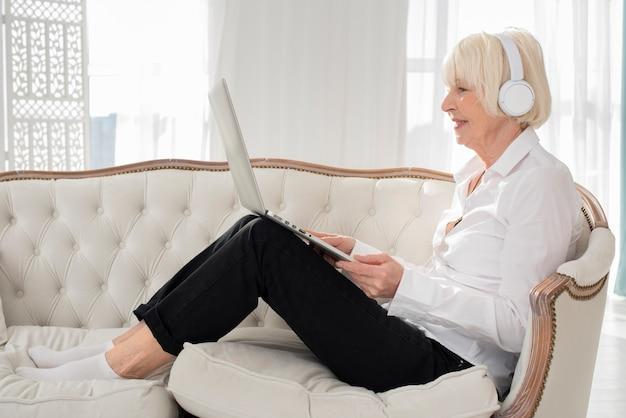 Glückliche alte frau, die auf sofa mit kopfhörern und laptop sitzt Kostenlose Fotos