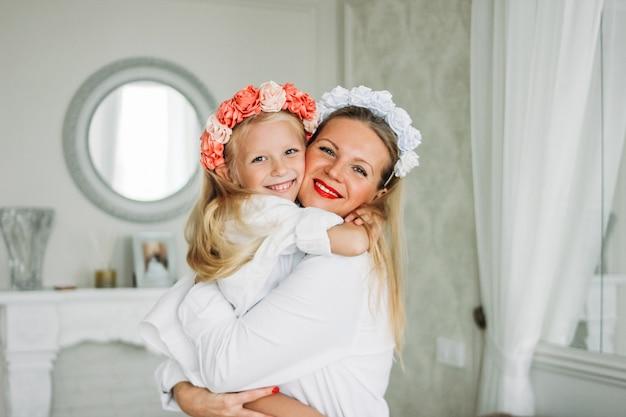 Glückliche angemessene lange haarmutter und nette tochter in den kränzen von blumen am wohnzimmer, glücklicher familienlebensstil Premium Fotos