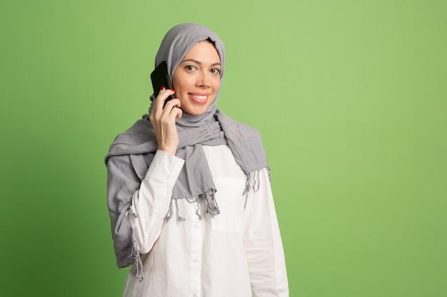 Glückliche arabische frau im hijab mit handy. porträt des lächelnden mädchens, das im grünen studio aufwirft. Kostenlose Fotos