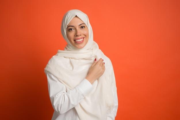 Glückliche arabische frau im hijab. porträt des lächelnden mädchens, das am roten studiohintergrund aufwirft. junge emotionale frau. die menschlichen emotionen, gesichtsausdruck konzept. vorderansicht. Kostenlose Fotos
