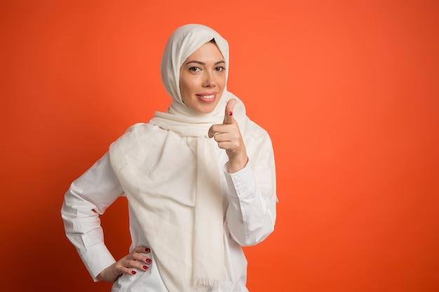 Glückliche arabische frau im hijab. porträt des lächelnden mädchens, das auf kamera am roten studiohintergrund zeigt. junge emotionale frau. menschliche emotionen, gesichtsausdruck konzept. Kostenlose Fotos