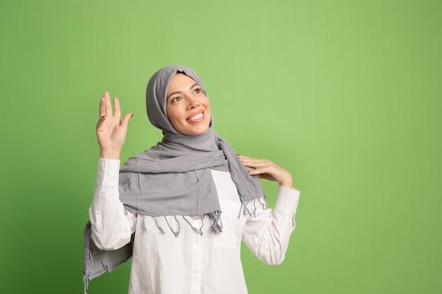 Glückliche arabische frau im hijab. porträt des lächelnden mädchens, das im grünen studio aufwirft. Kostenlose Fotos