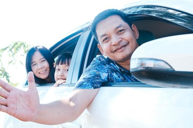 Glückliche asiatische familie, die im auto sitzt und aus den fenstern schaut Premium Fotos