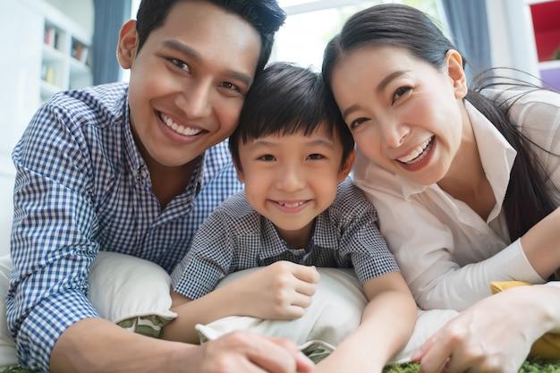 Glückliche asiatische familie, die zusammen zeit auf sofa im wohnzimmer verbringt. Premium Fotos