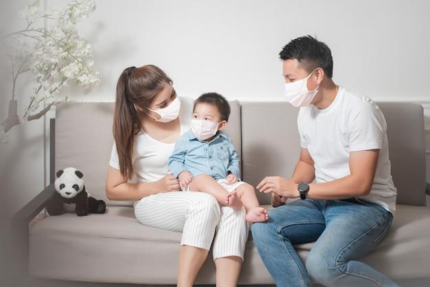 Glückliche asiatische familie tragen gesichtsmaske bleiben zu hause Premium Fotos