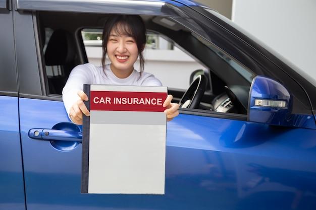 Glückliche asiatische frau, die autoversicherungsdokumentbuch hält und im auto, sicherheitsfahrzeug- und schutzkunden-personenkonzept sitzt Premium Fotos