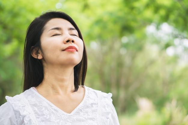 Glückliche asiatische frau, die draußen frischluft atmet Premium Fotos