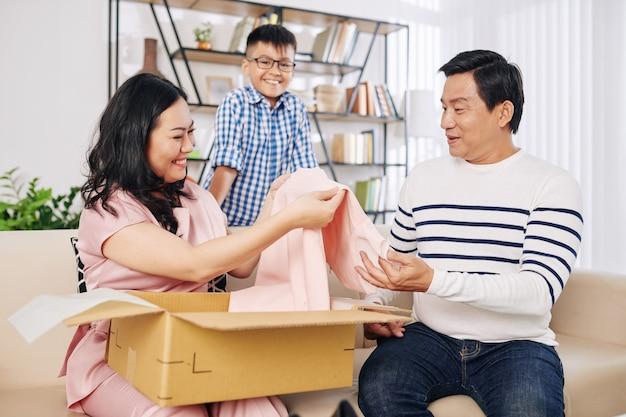 Glückliche asiatische frau, die hellrosa kleid aus geschenkbox von ihrem ehemann und jugendlichen sohn nimmt Premium Fotos