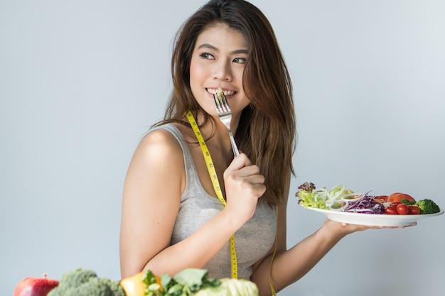 Glückliche asiatische frau, die organischen salat isst. Premium Fotos