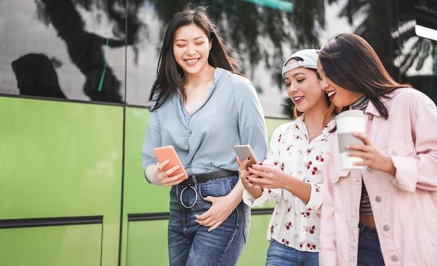 Glückliche asiatische freunde, die smartphones am busbahnhof verwenden. junge studenten, die spaß mit technologietrends nach der schule haben Premium Fotos